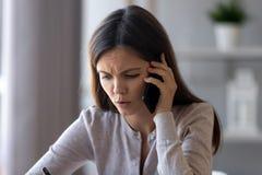 Mulher interessada séria que fala no telefone que ajuda resolvendo o problema foto de stock