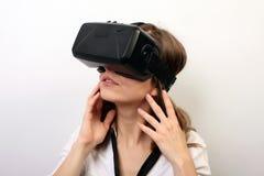 Mulher intrigada em uma camisa formal branca, auriculares vestindo da realidade virtual 3D da falha VR de Oculus, explorando um j Imagens de Stock Royalty Free
