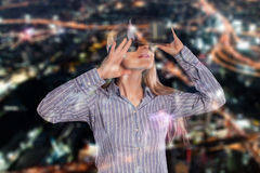Mulher intrigada na camisa cinzenta que veste auriculares da realidade virtual 3D Foto de Stock Royalty Free