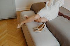 A mulher irreconhecível cansado no vestido branco, decola as sapatas do salto alto quando vier em casa após o dia de trabalho dur Fotografia de Stock Royalty Free