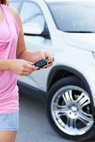 Mulher irreconhecível com a chave de ignição que está perto do carro novo Imagens de Stock
