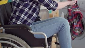 A mulher irreconhecível desabilitou em uma cadeira de rodas usando uma máquina de lavar filme