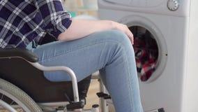 A mulher irreconhec?vel desabilitou em uma cadeira de rodas usando um fim da m?quina de lavar acima filme