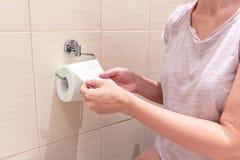 Mulher irreconhecível, sentando-se em um toalete e em uma rebobinação e para rasgar fora um papel higiênico Imagem do conceito de foto de stock royalty free