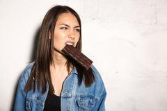 Mulher irritada do moderno que come o chocolate fotografia de stock