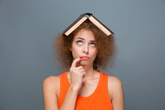 Mulher irritada encaracolado que olha engraçada com o livro na cabeça Foto de Stock