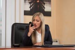Mulher irritada na gritaria do vestuário formal no telefone Fotografia de Stock Royalty Free
