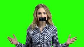 Mulher irritada nova com a fita preta em sua boca video estoque