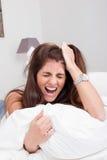 Mulher irritada nova na cama que puxa seu cabelo e que grita Foto de Stock