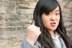 Mulher irritada por uma parede de pedra Fotos de Stock Royalty Free