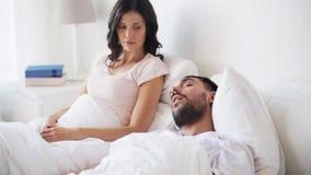 Mulher irritada que acorda o homem que dorme na cama vídeos de arquivo
