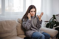 Mulher irritada que discute durante um telefonema imagem de stock