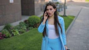 Mulher irritada, irritada que falam pelo telefone na cidade e smartphone de jogo filme