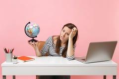 A mulher irritada que inclina-se disponível guardando o globo que manda problemas com quando do planeamento das férias sentar-se, fotografia de stock