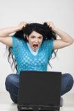Mulher irritada que retira o cabelo na frente do portátil Fotografia de Stock Royalty Free