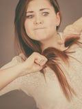 Mulher irritada que tenta escovar seu cabelo fotos de stock royalty free