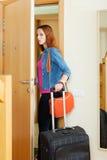 A mulher irritada sae em casa com a mala de viagem Foto de Stock