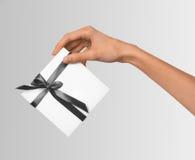 A mulher isolada entrega guardar a caixa branca atual do feriado com Grey Ribbon em um fundo branco Imagens de Stock