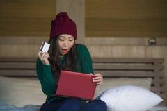 Mulher japonesa asiática feliz bonita nova no chapéu do inverno relaxado no cartão de crédito da terra arrendada da cama usando o fotografia de stock