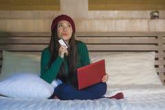 Mulher japonesa asiática feliz bonita nova no chapéu do inverno relaxado no cartão de crédito da terra arrendada da cama usando o foto de stock royalty free