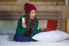 Mulher japonesa asiática feliz bonita nova no chapéu do inverno relaxado no cartão de crédito da terra arrendada da cama usando o imagem de stock