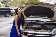 Mulher japonesa asiática preocupada no esforço encalhada na borda da estrada da rua com a falha no motor do carro que tem o probl imagens de stock