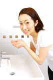 A mulher japonesa nova lava sua cara no lavabos Imagens de Stock Royalty Free