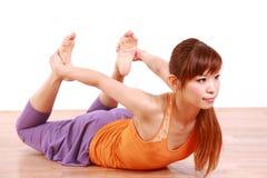 Mulher japonesa nova que faz a pose da rã da IOGA Imagem de Stock