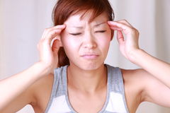 A mulher japonesa nova sofre da dor principal Imagens de Stock
