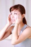 A mulher japonesa nova sofre da dor principal Fotografia de Stock