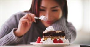 Mulher japonesa que come o bolo em casa imagem de stock