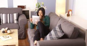 Mulher japonesa que usa a tabuleta no sofá Fotografia de Stock Royalty Free