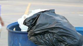 A mulher joga desperdícios A lata de lixo completa com os grandes sacos de lixo completamente do alimento e do desperdício restan filme