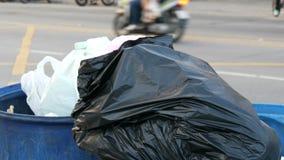 A mulher joga a garrafa plástica A lata de lixo completa com os grandes sacos de lixo completamente do alimento e do desperdício  video estoque