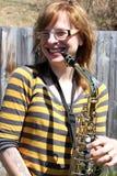 A mulher joga o saxofone ao ar livre foto de stock royalty free