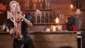 A mulher jogar um saxofone quando um homem no vinho das bebidas da audiência filme