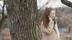 Mulher jovem de sorriso grávida na luz retro do vintage - o revestimento bege marrom faz uma chamada com o telefone celular dentr filme