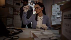 Mulher judicial do cientista nas luvas que examina a bala da evidência, encontrando o indício foto de stock