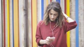 Mulher justa nova do cabelo que veste uma camiseta vermelha que está perto de uma parede colorida que escuta a música Fotografia de Stock Royalty Free
