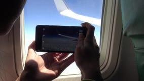 mulher 4K asiática que usa o telefone esperto pela janela um avião filme