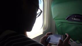 mulher 4K asiática que usa o telefone esperto pela janela um avião video estoque