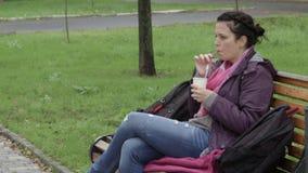 a mulher 4K está bebendo o café no parque em um banco vídeos de arquivo