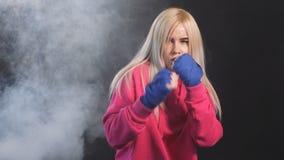 Mulher kickboxing loura concentrada no treinamento no estúdio da aptidão, movimento lento Forma??o duramente video estoque
