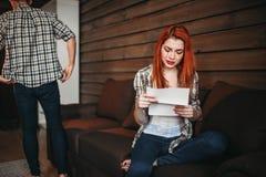A mulher lê a letra e o grito, pares no conflito imagem de stock royalty free