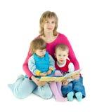 A mulher lê o livro às crianças imagem de stock