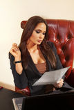 A mulher lê o original no escritório Fotos de Stock Royalty Free
