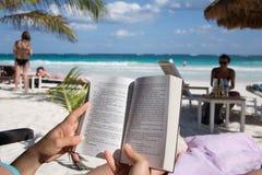 A mulher lê um livro na praia de Tulum as Caraíbas Foto de Stock