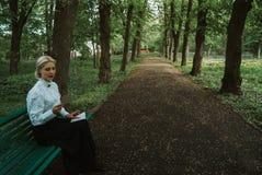 A mulher lê uma letra de papel em um banco imagens de stock
