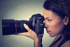Mulher lateral do perfil que toma imagens com câmera profissional Tiro do estúdio Fotografia de Stock