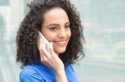 Mulher latin atrativa com cabelo encaracolado no telefone na cidade fotos de stock royalty free
